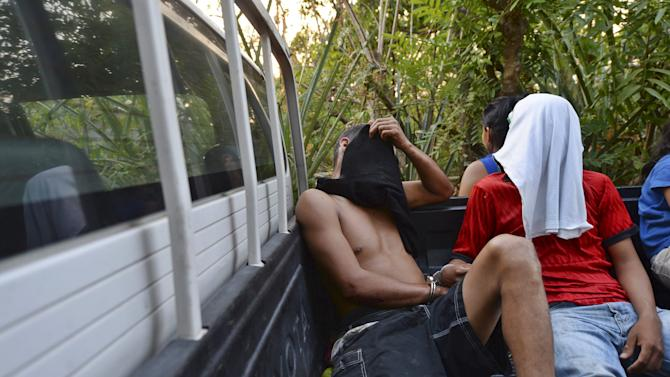 Suspected members of the Barrio 18 gang are detained by policemen in the town of Zacatecoluca.