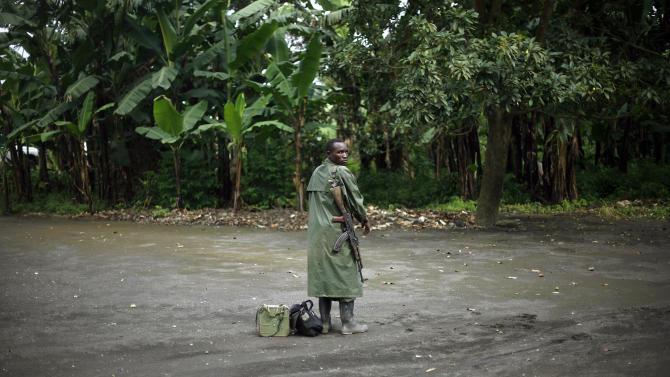 """A M23 rebel stands with his weapon as M23 rebels withdraw from the Masisi and Sake areas in the eastern Congo town of Sake, some 27 kms west of Goma, Friday Nov. 30, 2012. Rebels in Congo believed to be backed by Rwanda postponed their departure Friday from the key eastern city of Goma by 48 hours for """"logistical reasons,"""" defying for a second time an ultimatum set by neighboring African countries and backed by Western diplomats. The delay raises the possibility that the M23 rebels don't intend to leave the city they seized last week, giving credence to a United Nations Group of Experts report which argues that neighboring Rwanda is using the rebels as a proxy to annex territory in mineral-rich eastern Congo.(AP Photo/Jerome Delay)"""
