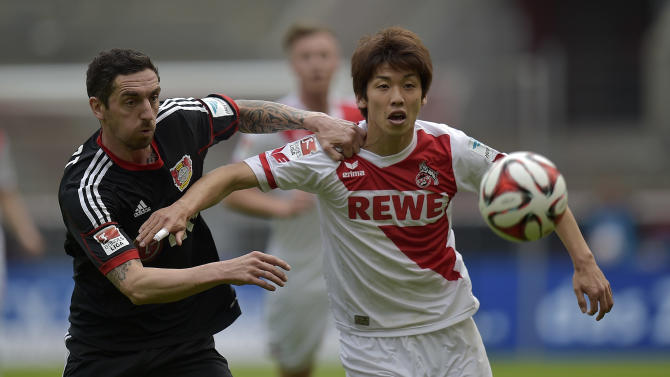 Cologne's Yuya Osako from Japan, right, and Leverkusen's Roberto Hilbert challenge for the ball during the German first division Bundesliga soccer match between 1. FC Cologne and Bayer Leverkusen in Cologne, Germany, Saturday, April 25, 2015. (AP Photo/Martin Meissner)