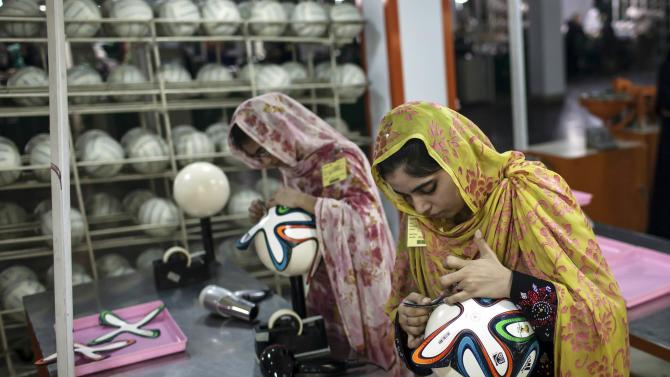 An employee adjusts outer panels on a soccer ball inside the soccer ball factory that produces official match balls for 2014 World Cup in Brazil, in Sialkot, Punjab province