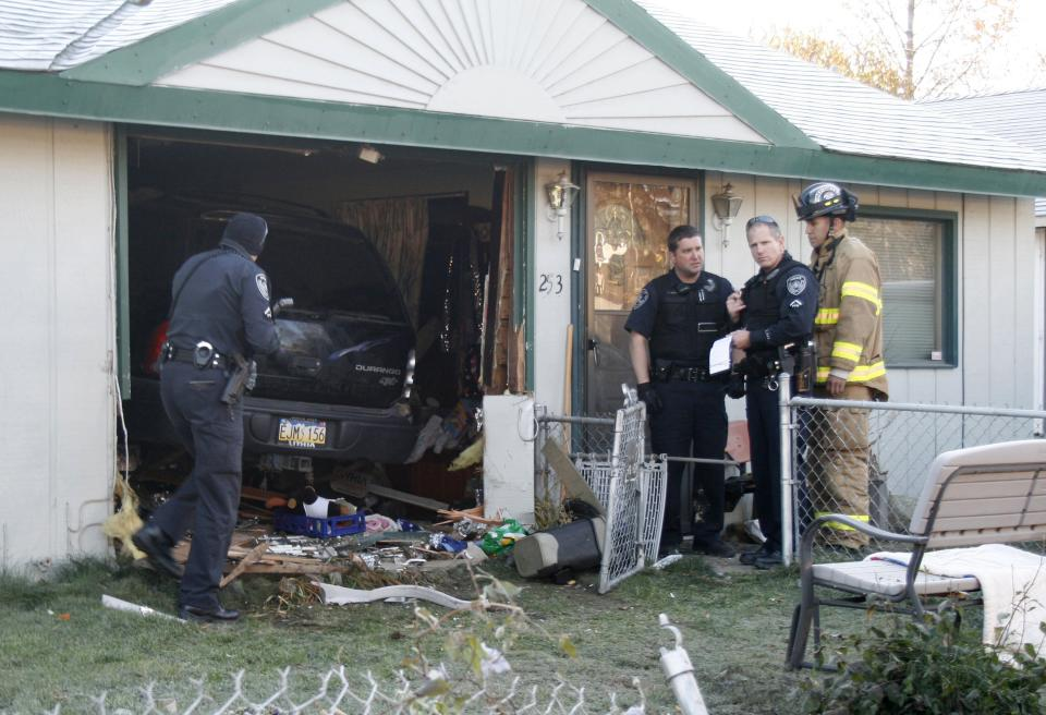 A vehicle drove completely into a home in Anchorage, Alaska, on Tuesday, Oct. 11, 2011, barely missing the homeowner, who was sitting in a chair that the SUV missed by inches. The driver was taken to the hospital with minor injuries; the homeowner was skaken up but unhurt. (AP Photo/Mark Thiessen)