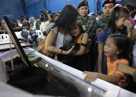 Children cry in front of the casket for their father, one of the slain members of the Special Action Force (SAF) who were killed in Sunday's clash with Muslim rebels, during a service inside a police headquarters in Taguig city