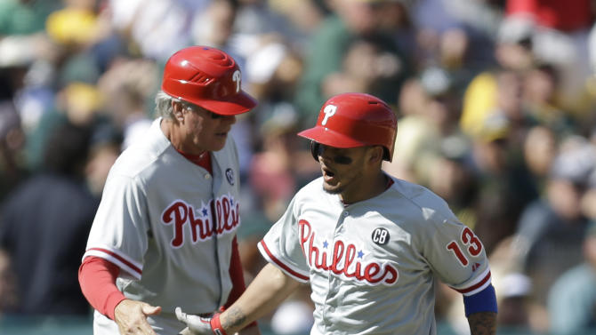 Philadelphia Phillies' Freddy Galvis, right, is congratulated by third base coach Pete Mackanin after Galvis hit a two run home run off Oakland Athletics' Dan Otero in the seventh inning of a baseball game Saturday, Sept. 20, 2014, in Oakland, Calif. (AP Photo/Ben Margot)