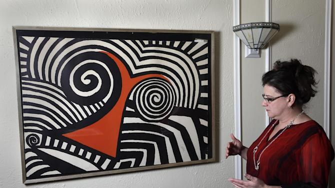 In this Wednesday, Nov. 28, 2012 photo, Karen Mallet stands by her Alexander Calder print in her Shorewood, Wis., home. Mallet bought the print for $12.34 at a Goodwill thrift store in Milwaukee. It turned out to be a lithograph by the American artist Alexander Calder worth $9,000. (AP Photo/Morry Gash)