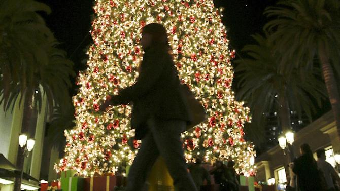 In this Thursday, Dec. 20, 2012, photo, a holiday shopper walks past a large Christmas tree at Fashion Island shopping center in Newport Beach, Calif. A last-minute surge in spending helped many major U.S. retailers report better-than-expected sales in December, a relief for stores that make up to 40 percent of annual revenue during the holiday period.  (AP Photo/Chris Carlson)