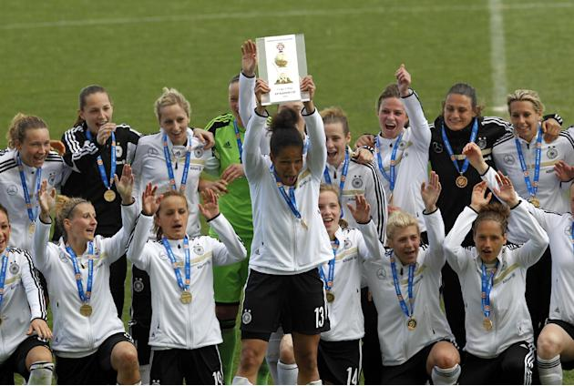 Germany's captain Celia Sasic, center, lifts up the trophy to celebrate with teammate after winning the women's soccer Algarve Cup at the Algarve stadium, outside Faro, southern Portugal, Wedn