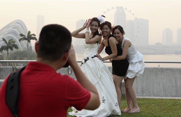 A bride and her bridesmaids pose for a photographer in the hazy skyline of the Singapore Flyer at Marina Barrage