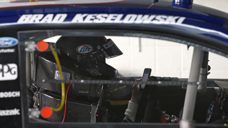 Brad Keselowski checks his phone as he sits in his car as the crew works on it during testing for the NASCAR Sprint Cup auto racing series at Charlotte Motor Speedway in Concord, N.C., Tuesday, Dec. 11, 2012. (AP Photo/Chuck Burton)