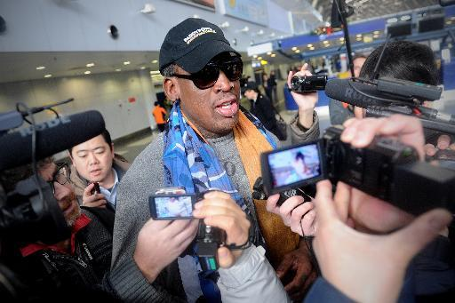 Former US NBA basketball player Dennis Rodman speaks to members of the media as he makes his way through Beijing's international airport on December 19, 2013