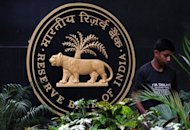 A gardener tends to plants at the Reserve Bank of India headquarters in Mumbai. India's central bank kept its key interest rates unchanged on Tuesday as predicted, but it delivered bleak forecasts for the slowing economy and warned about the country's deficits