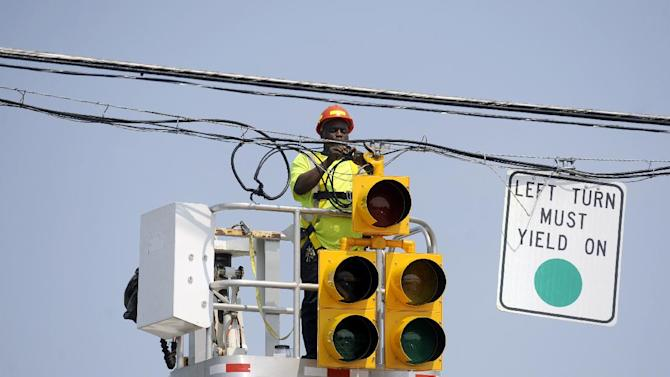 A Lynchburg City worker ties power lines above a traffic signal at Oakley and Memorial Avenues, July 1, 2012. Two days after storms tore across the eastern U.S., power outages were forcing people to get creative to stay cool in dangerously hot weather. Temperatures approached 100 degrees in many storm-stricken areas, and utility officials said the power will likely be out for several more days. (AP Photo/The News & Advance, Parker Michels-Boyce)