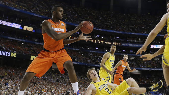 Syracuse's Rakeem Christmas (25) handles the ball as Michigan's Spike Albrecht (2) looks up during the first half of a semifinal in the the NCAA men's college basketball tournament Final Four, Saturday, April 6, 2013, in Atlanta. (AP Photo/Charlie Neibergall)