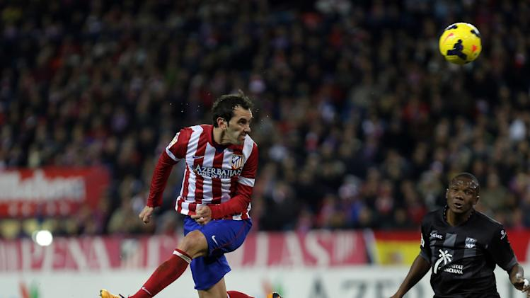 Atletico's Diego Godin, left, scores a goal during a Spanish La Liga soccer match between Atletico de Madrid and Levante at the Vicente Calderon stadium in Madrid, Spain, Saturday, Dec. 21, 2013