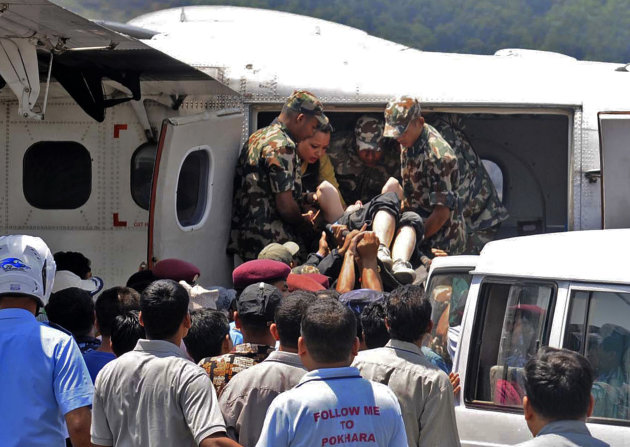 Nepalese army soldiers carry a survivor of a plane crash flown for treatment to the nearby city of Pokhara, Nepal, Monday, May 14, 2012. A plane crashed into a mountain in the Himalayas while trying to land at Jomsom Airport, 200 kilometers (125 miles) northwest of the capital, Katmandu, Monday, killing 15 people and critically injuring six. (AP Photo/Krishnamani Baral)