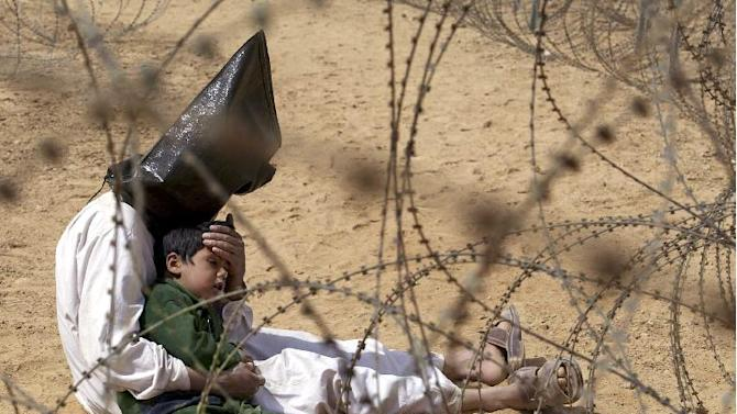 FILE - An Iraqi prisoner of war comforts his 4-year-old son at a regrouping center for POWs captured by the U.S. Army 101st Airborne Division near Najaf, Iraq on March 31, 2003. The man was seized in An Najaf with his son, and the U.S. military did not want to separate the two. (AP Photo/Jean-Marc Bouju, File)