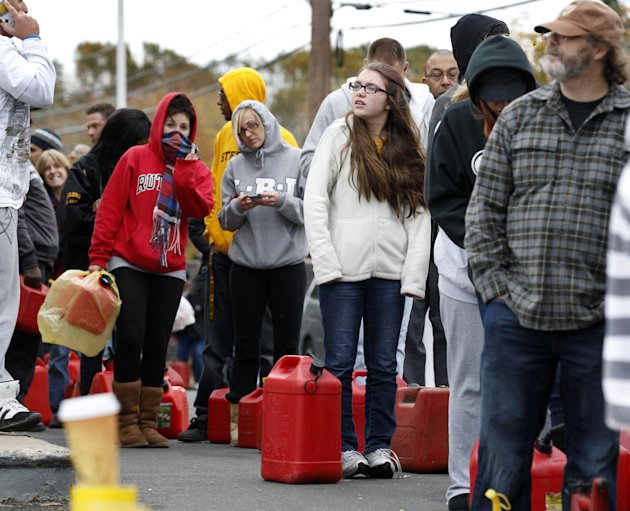 As temperatures begin to drop, people wait in line to fill containers with gas at a Shell gasoline filling station Thursday, Nov. 1, 2012, in Keyport, N.J. In parts of New York and New Jersey, drivers