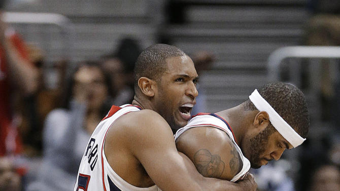 Atlanta Hawks' Al Horford, left, and Josh Smith react after a Hawks basket in overtime of an NBA basketball game against the Boston Celtics on Friday, Jan. 25, 2013, in Atlanta.Atlanta won 123-111 in double-overtime. (AP Photo/John Bazemore)