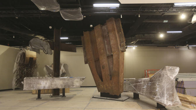 The 'Cross', left, intersecting steel beams found in the rubble of 6 World Trade Center and a fragment of a trident column, center, one of 84 that formed the exterior structure of each tower are displayed during a media tour of the National September 11 Memorial and Museum, Friday, Sept. 6, 2013, in New York. Construction is racing ahead inside the museum as the 12th anniversary of the Sept. 11, 2001 attacks draws near. Several more large artifacts have been installed in the cavernous space below the World Trade Center memorial plaza. (AP Photo/Mary Altaffer)