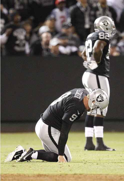 Oakland Raiders punter Shane Lechler (9) kneels on the ground after having a punt blocked by San Diego Chargers tight end Dante Rosario during the second half of an NFL football game in Oakland, Calif