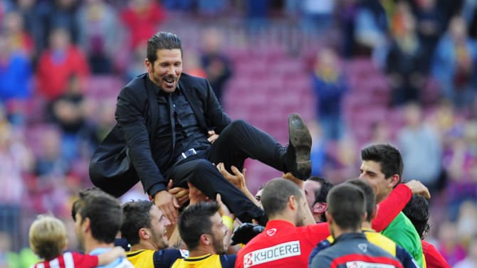 Plauers lift Atletico's coach Diego Simeone from Argentina after a Spanish La Liga soccer match between FC Barcelona and Atletico Madrid at the Camp Nou stadium in Barcelona, Spain, Saturday, May 17, 2014. Atletico clinched its first league title in 18 years after a 1-1 draw.(AP Photo/Manu Fernandez)