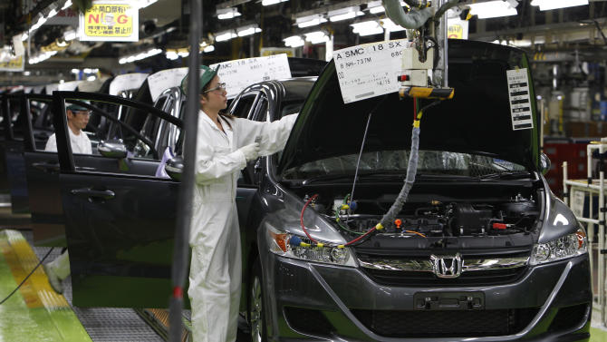 In this April 18, 2011 photo, workers give the final checkup on the cars of Honda Accord Tourer at Honda Motor Co.'s Saitama Factory in Sayama, north of Tokyo, Monday, April 18, 2011 as the Japanese automaker resumed limited production on April 11 at the factory following the March 11 earthquake and tsunami. Honda said Thursday, April 28, 2011 its quarterly profit dropped 38.3 percent due to a slump in car production following last month's disasters. (AP Photo/Shizuo Kambayashi)