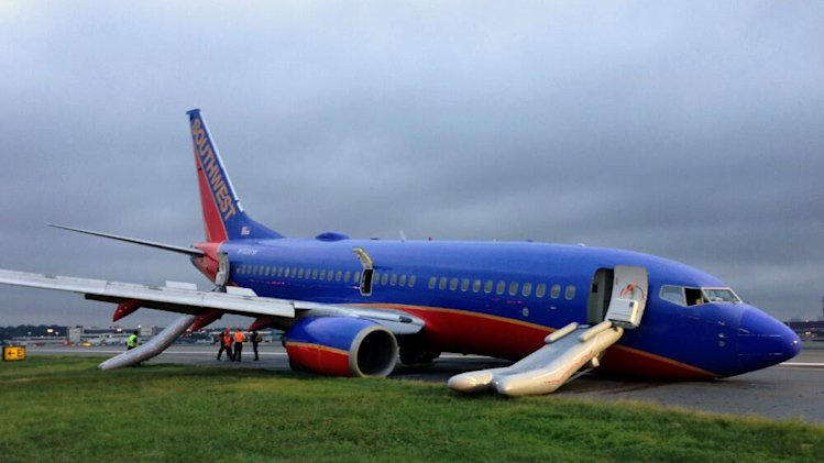 NTSB agents investigate an accident involving nose-gear collapse of a southwest airlines plane, Monday, July 22, 2013, in New York. The Federal Aviation Administration says the plane landed safely. (AP Photo/NTSB)