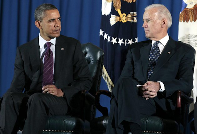 President Barack Obama and Vice President Joe Biden look at each other as they participate in a ceremony at Andrews Air Force Base, Md., Tuesday, Dec. 20, 2011, marking the return of the United States Forces-Iraq Colors and the end of the war in Iraq. (AP Photo/Carolyn Kaster)