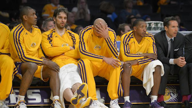 Los Angeles Lakers, from left, forward Metta World Peace, left, forward Pau Gasol, of Spain, center Robert Sacre, guard Chris Duhon and guard Steve Nash watch from the bench late in the second half in Game 3 of a first-round NBA basketball playoff series against the San Antonio Spurs, Friday, April 26, 2013, in Los Angeles. The Spurs won 120-89. (AP Photo/Mark J. Terrill)