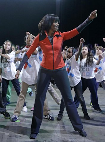 First lady Michelle Obama exercises with children from Chicago Public Schools, in her hometown of Chicago, Thursday, Feb. 28, 2013, as she makes a major announcement helping to bring back physical activity to area schools, while celebrating the third anniversary of her &#39;Lets Move&#39; program. (AP Photo/M. Spencer Green)