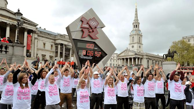 West End theater workers and performers dance in front of the Olympic countdown clock to mark the 100-day countdown, in Trafalgar Square, central London, Wednesday, April 18, 2012. With 100 days to go until the 2012 London Olympics, the city's theater community is increasingly confident that culture won't suffer during a summer devoted to celebrating sport. (AP Photo/PA, John Stillwell) UNITED KINGDOM OUT, NO SALES, NO ARCHIVE