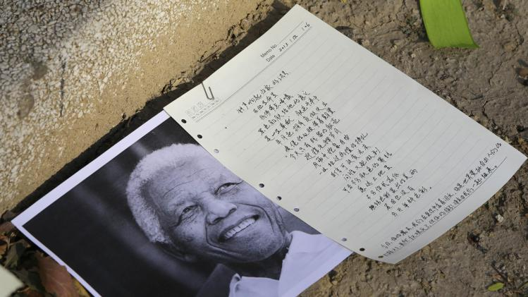 A picture and a letter are placed in front of the South African Embassy to pay tribute to former South African President Mandela, in Beijing