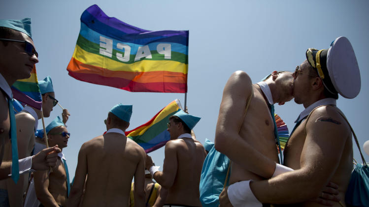 Israeli dancers kiss each other during the annual Gay Pride Parade on a street of Tel Aviv, Israel, Friday, June 13, 2014. Shirtless Israeli men, colorfully dressed drag queens and others partied Friday through central Tel Aviv as it celebrates the week-long event that supports lesbian, gay, bisexual and transgender people and their supporters, also known as the LGBT community. (AP Photo/Oded Balilty)