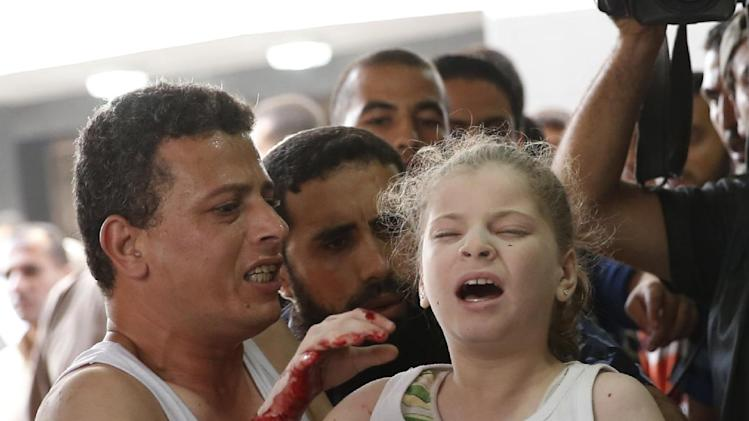A Palestinian carries a wounded girl in the emergency room of Shifa hospital in Gaza City, northern Gaza Strip, Sunday, July 20, 2014. Hundreds of panicked residents have fled a Gaza City neighborhood which they say has come under heavy tank fire from Israeli forces. Some reported seeing dead and wounded in the streets, with ambulances unable to reach the area. Israel widened its ground offensive early Sunday, sending more troops into the Hamas-ruled territory to destroy tunnels used by the Islamic militants to try to sneak into Israe(AP Photo/Lefteris Pitarakis)
