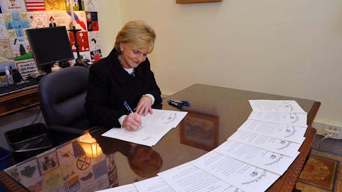 In a photo provided by the Office of the governor, outgoing North Carolina Gov. Beverly Perdue signs pardons Monday, Dec. 31. 2012 to the Wilmington 10, a group wrongly convicted 40 years ago in a notorious Civil Rights-era prosecution that led to accusations of the state holding political prisoners. Perdue issued pardons of innocence Monday for the nine black men and one white woman who combined were sentenced to nearly 300 years in prison for the 1971 firebombing of a Wilmington grocery store after police shot a black teenager. The pardon means the state no longer thinks the 10 _ four of whom have since died _ committed a crime. (AP Photo/North Carolina Governors Office)