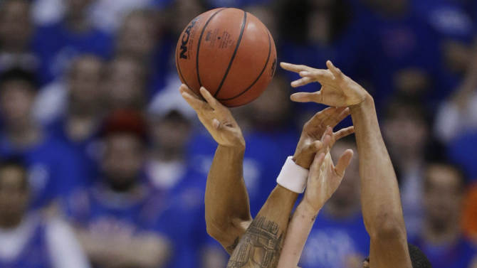 Kansas guard Travis Releford (24) reaches for a rebound next to Oklahoma State forward Michael Cobbins (20) and center Philip Jurick (44) during the first half of an NCAA college basketball game in Lawrence, Kan., Saturday, Feb. 2, 2013. (AP Photo/Orlin Wagner)