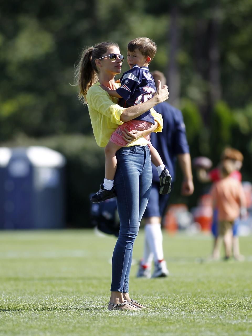 Gisele Bundchen comforts her son Benjamin after he was hurt playing football, following a joint workout with the Tampa Bay Buccaneers and the New England Patriots at NFL football training camp, in Foxborough, Mass., Thursday, Aug. 15, 2013. (AP Photo/Stew Milne)
