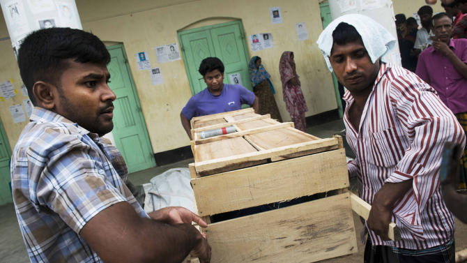 Bangladeshi relatives prepare to load onto a truck a coffin containing the body of a victim killed in the April 24 garment factory building collapse in Savar, near Dhaka, Bangladesh, Sunday, May 12, 2013. Search teams resumed their rain-interrupted work Sunday as the death toll from the collapse continued to climb past 1,100. (AP Photo/Ismail Ferdous)