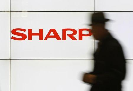 A pedestrian walks past a logo of Sharp Corp at a train station in Tokyo