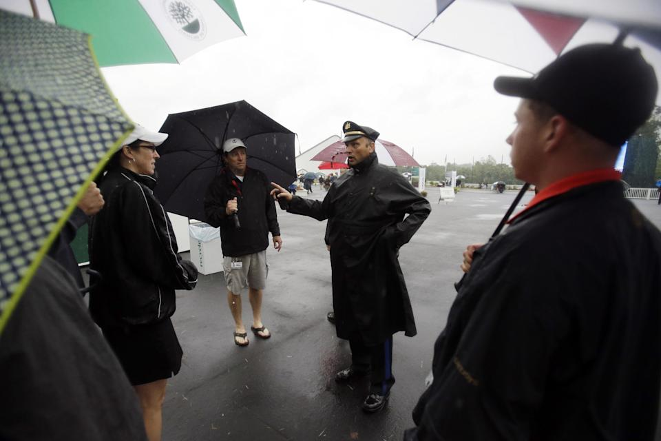 A police officer directs spectators off the course as weather delays the first round of the U.S. Open golf tournament at Merion Golf Club, Thursday, June 13, 2013, in Ardmore, Pa. (AP Photo/Gene J. Puskar)
