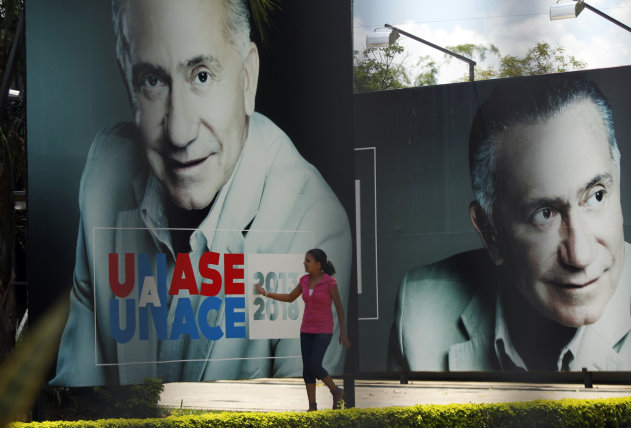 A woman touches a campaign poster of presidential candidate former Gen. Lino Cesar Oviedo outside the UNACE (National Union of Ethical Citizens) party headquarters in Asuncion, Paraguay, Sunday, Feb. 3, 2013. Oviedo was killed in a helicopter crash Saturday night, authorities said Sunday, ending a dramatic political career that included coups and repeated attempts to lead Paraguay. (AP Photo/Jorge Saenz)