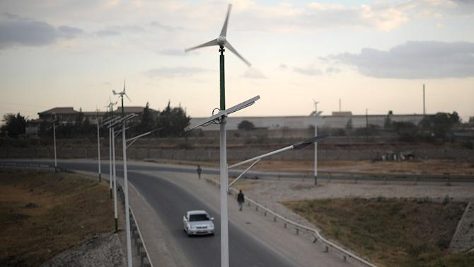 Street lamps powered by wind and solar energy line the side of a road leading from Athi-river town in Machakos county, approximately 25 kilometres from the Kenyan capital Nairobi, on August 19, 2015