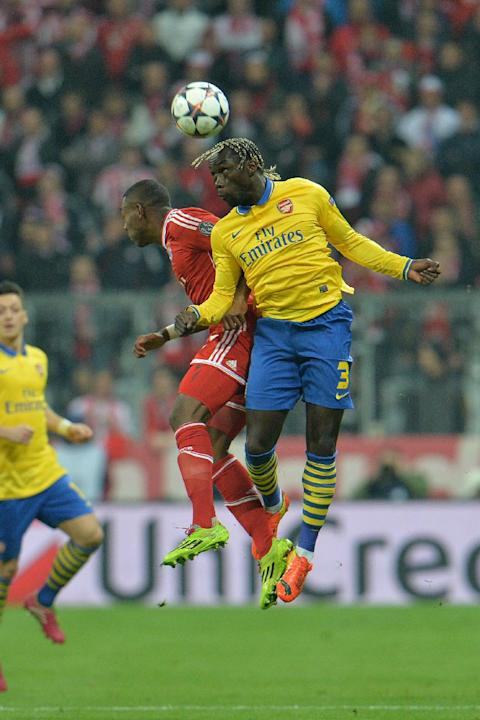 Bayern's David Alaba of Austria, left, and Arsenal's Bacary Sagna challenge for the ball during the Champions League round of the last 16 second leg soccer match between FC Bayern Munich and A
