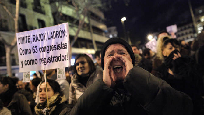 FILE _ In this Jan. 18, 2013 file photo, people shout slogans as they hold a banner reading 'Spain's Prime Minister, resign thief!' as they protest against corruption outside the Popular Party's headquarters in central Madrid. After two years of recession, harsh austerity programs, sky-high unemployment and an unstable footing on the world's markets. Now comes a corruption scandal that has shaken the government to its core. And it's raising questions whether Prime Minister Mariano Rajoy can survive the fallout from allegations that he and others benefited from years of slush fund handouts.(AP Photo/Andres Kudacki, File)