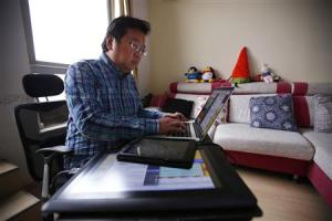 Chinese cartoonist Wang Liming uses his computer inside his apartment before an interview with Reuters in Beijing