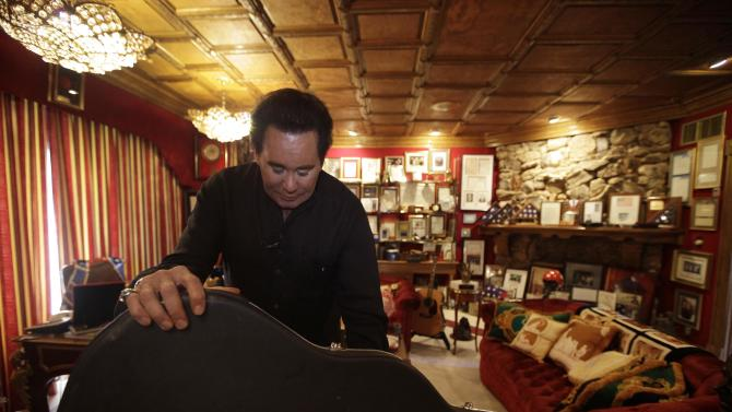 In this photo taken Friday, Nov. 12, 2010, Wayne Newton shows some of the memorabilia in the Red Room during an interview at his home in Las Vegas. Newton, the former two-bit lounge singer turned Las Vegas icon, hopes to create a Wayne Newton museum at his home. His neighbors, however, are less than thankful about the idea of noisy tour buses, unyielding traffic and inane gift shops flooding their affluent neighborhood of ranches and megamansions just six miles from the Las Vegas Strip.  (AP Photo/Julie Jacobson)