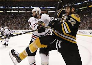 Bruins' Thornton is hit into the boards by Blackhawks' Seabrook in Game 3 of their NHL Stanley Cup Finals in Boston