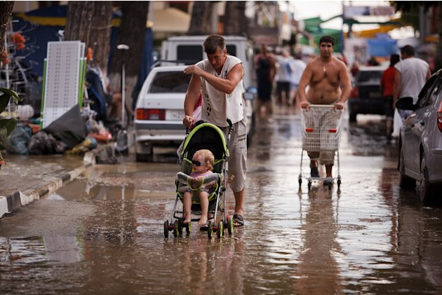 Gente camina por las calles llenas de agua y lodo luego de una inundacin en Gelendzhik, centro vacacional del Mar Muerto, en el sur de Rusia, el sbado 7 de julio de 2012. Las lluvias torrenciales en