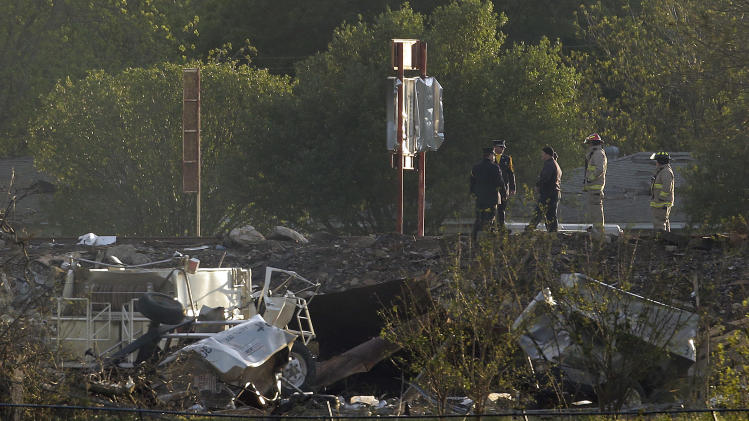 Workers walk among debris Thursday, April 18, 2013, a day after an explosion at a fertilizer plant in West, Texas. The massive explosion at the West Fertilizer Co. Wednesday night killed as many as 15 people and injured more than 160. (AP Photo/Charlie Riedel)