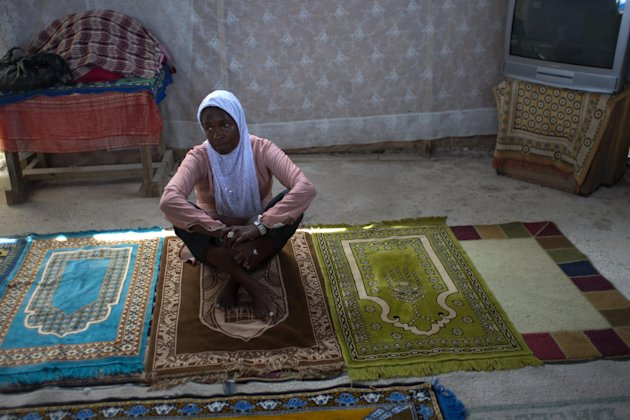 In this Sept. 28, 2012 photo, Darlene Derosier, 43, a Muslim, sits on a prayer rug at the Al-Fattah Mosque in Gressier, Haiti. Islam has won a growing number of followers in this impoverished country, especially after the catastrophic earthquake in 2010 that killed hundreds of thousands and left millions more homeless. Derosier said what's helped pull her through all the grief has been her faith, but not of the Catholic, Protestant or even Voodoo that's dominated this island country. Instead, she's converted to a new religion here, Islam, and built a small neighborhood mosque out of cinderblocks and plywood, where some 60 Muslims pray daily. (AP Photo/Dieu Nalio Chery)