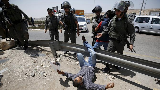 Palestinian protester falls on the ground after being pushed by Israeli border policemen during a protest near Ramallah